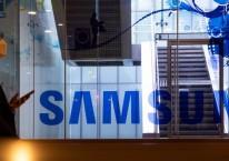Seorang pria yang mengenakan masker pelindung berjalan melewati papan nama Samsung Electronics Co di Seoul, Korea Selatan. SeongJoon Cho/Bloomberg