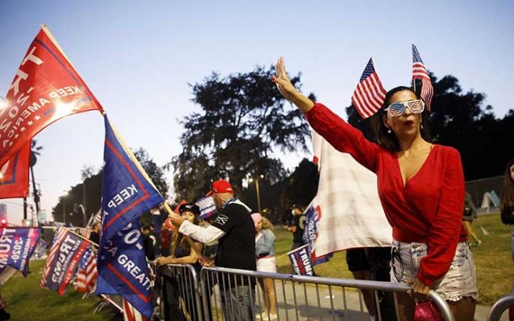 Demonstran mengibarkan bendera kampanye Trump pada rapat umum selama pemilihan Presiden 2020 di Beverly Hills, California, AS, Selasa (3/11/2020).  Bloomberg - Patrick T. Fallon