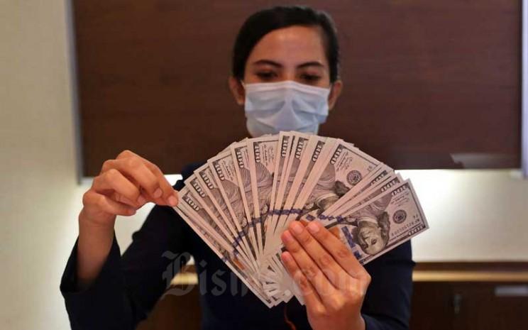 Karyawan menunjukan dolar AS di Jakarta, Rabu (11/11/2020). Nilai tukar Rupiah terhadap dolar AS pada perdagangan Rabu (11/11) ditutup melemah 0,2 persen atau 27,5 poin ke level Rp14.085 per dolar AS. Bisnis - Eusebio Chrysnamurti