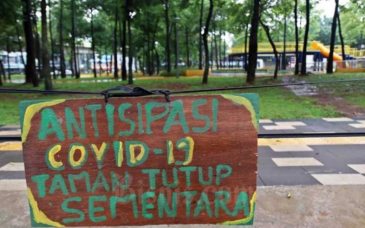 Informasi mengenai penutupan sementara taman terpampang di Taman Ayodya, Jakarta, Rabu (18/3/2020). Pemerintah Provinsi DKI Jakarta menutup sementara seluruh taman di Ibu Kota untuk mencegah penyebaran virus corona (COVID-19). Bisnis - Eusebio Chrysnamurti
