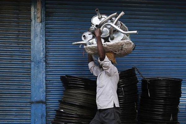 Seorang pekerja membawa sejumlah knalpot mobil di pasar suku cadang otomotif - Reuters/Adnan Abidi