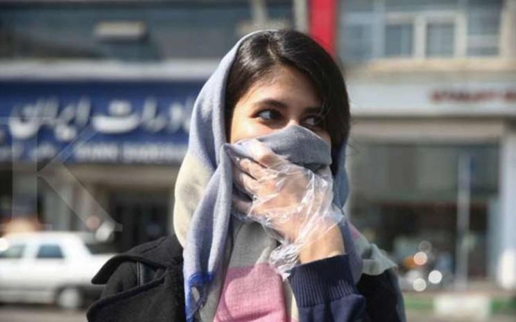 Seorang perempuan Iran mengenakan masker di Teheran pada 5 Maret 2020./Antara - Reuters