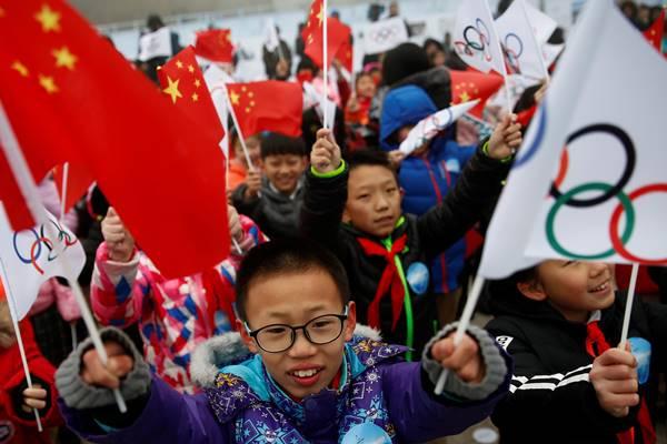 Anak-anak melambaikan bendera China dan Olimpiade selama upacara menandai dimulainya tur bendera Olimpiade menjelang Olimpiade Beijing 2022 dan Paralimpiade Musim Dingin di Badaling, Tembok Besar di distrik Yanqing, Beijing, China, 27 Februari 2018 . - Reuters