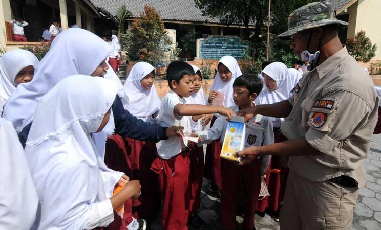 Petugas Badan Penanggulangan Bencana Daerah (BPBD) Kabupaten Boyolali membagikan masker kepada anak sekolah di SD N 1 Ringinlarik, Musuk, Boyolali, Jawa Tengah, Selasa (3/3/2020). ANTARA FOTO - Aloysius Jarot Nugroho