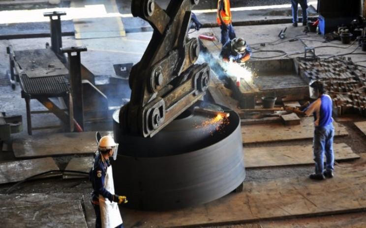 Pekerja memotong lempengan baja panas di pabrik pembuatan hot rolled coil (HRC) PT Krakatau Steel (Persero) Tbk di Cilegon, Banten. ANTARA - ASEP FATHULRAHMAN