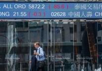 Pejalan kaki berjalan di depan kompleks Exchange Square, yang menjadi lokasi Hong Kong Stock Exchange, di Hong Kong, China, Jumat (29/5/2020)./Bloomberg-Lam Yik
