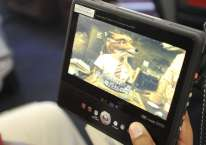 Seorang penumpang menonton film menggunakan DVD player portabel di pesawat Delta Air Lines Inc. di Hartsfield-Jackson Atlanta International Airport di Atlanta, AS, Jumat (17/12/2010)./Bloomberg-Erik S. Lesser