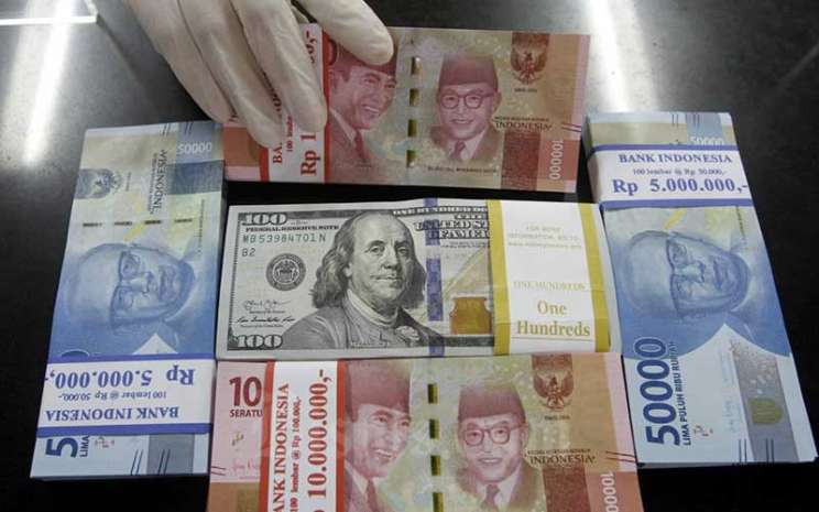 Karyawati menunjukan Uang Rupiah dan Dollar AS di salah satu kantor cabang Bank BNI di Jakarta, Kamis (3/9/2020). - Bisnis/Himawan L Nugraha