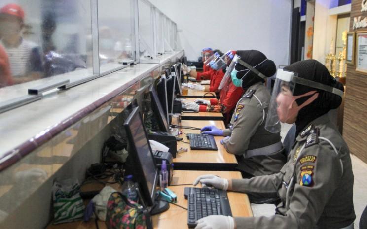 Sejumlah petugas mengenakan pelindung wajah dan masker. Kini jadwal pelayanan Samsat di Ruko Grand Square bisa tentatif menyesuaikan banyaknya pengunjung yang perlu dilayani. ANTARA