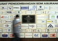 Karyawan beraktifitas di dekat deretan logo-logo perusahaan asuransi di Kantor Asosiasi Asuransi Umum Indonesia (AAUI) di Jakarta, Selasa (22/9/2020). Bisnis/Himawan L Nugraha