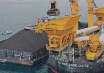 Aktivitas pemindahan muatan batu bara dari tongkang ke kapal induk dengan floating crane./indikaenergy.co.id