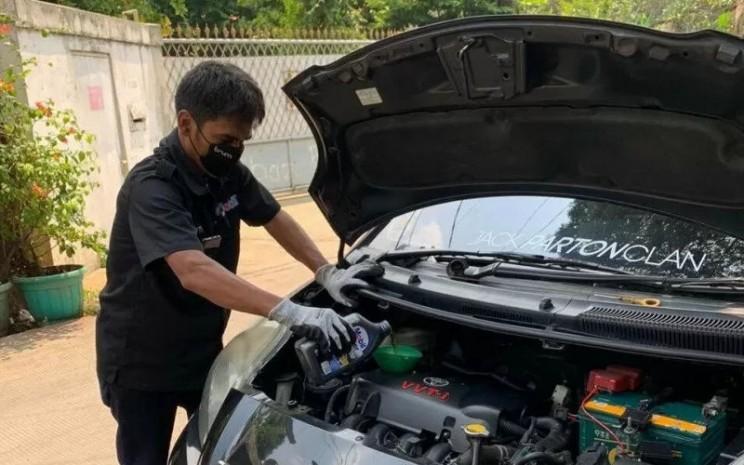 Mekanik mengganti oil kendaraan dengan Exxon Mobil Lubricant.  - ANTARA