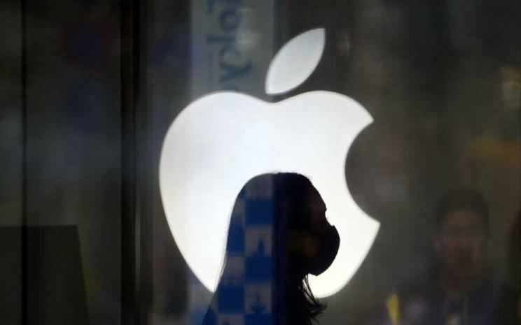 Siluet karyawan yang menggunakan masker di depan logo Apple Inc.  - Bloomberg/ Toru Hanai