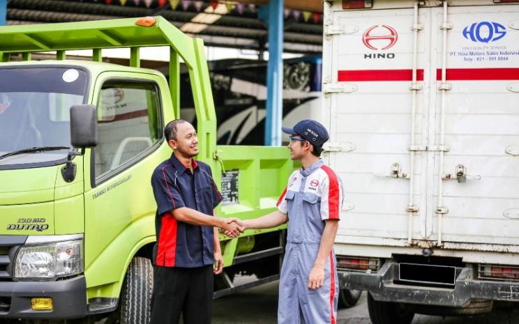 Serah terima unit kendaraan yang telah selesai perawatan dari mekanik kepada pelanggan di bengkel resmi Hino Motors.  - HINO