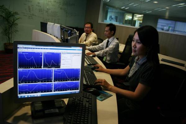 Sejumlah karyawan PT Bursa Berjangka Jakarta memantau transaksi perdagangan komoditas di Galeri JFX Jakarta. - Bisnis
