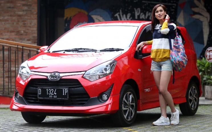 Model berpose di samping mobil Toyota New Agya di Bandung, Jawa Barat, Kamis (27/7/2019). - BISNIS.COM/RHN
