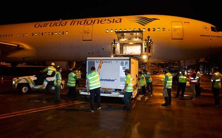 Petugas menurunkan kontainer berisi vaksin Covid-19 saat tiba di Bandara Soekarno-Hatta, tangerang, Banten, Minggu (6/12/2020). Sebanyak 1,2 juta dosis vaksin Covid-19 buatan perusahaan farmasi Sinovac, China, tiba di tanah air untuk selanjutnya akan diproses lebih lanjut ke Bio Farma selaku BUMN produsen vaksin. ANTARA FOTO - Dhemas Reviyanto