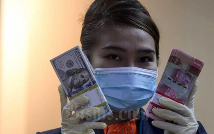 Karyawati menunjukan uang rupiah dan dolar AS di salah satu kantor cabang PT Bank Negara Indonesia (Persero) Tbk. di Jakarta, Selasa (5/1/2021). Bisnis - Arief Hermawan P