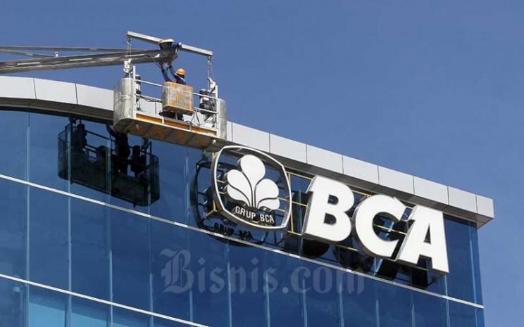 Pekerja membersihkan dinding kantor Bank Central Asia (BCA) di Makassar, Sulawesi Selatan, Selasa (16/6/2020). Bisnis - Paulus Tandi Bone