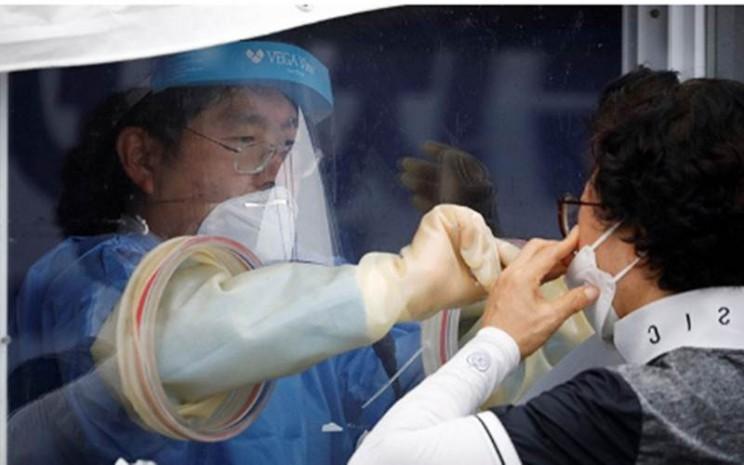 Seorang wanita menjalani tes virus corona (Covid-19) di sebuah klinik darurat di Seoul, Korea Selatan (26/8/2020)./Antara - Reuters/Kim Hong/Ji