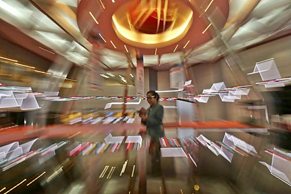 Karyawati berkomunikasi di dekat monitor pergerakan IHSG, di Bursa Efek Indonesia, Jakarta, Selasa (5/12). - JIBI/Nurul Hidayat