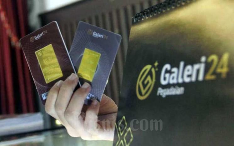 Karyawati menunjukan emas batangan di Galeri 24 Pegadaian, Jakarta, Selasa (8/12/2020). Bisnis - Himawan L Nugraha
