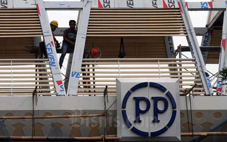Pekerja beraktifitas di dekat logo PT PP Properti Tbk. di Depok, Jawa Barat, Sabtu (9/5/2020). Bisnis - Dedi Gunawan