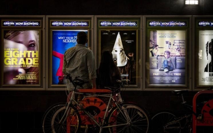 Calon penonton melihat poster film di luar Landmark Century Centre Cinema di Chicago, Illinois, AS, Kamis (16/8/2018). - Bloomberg/Christopher Dilts