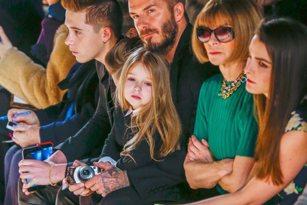 Harper Beckham (tengah) dipangku oleh David Beckham dalam sebuah acara peragaan busana - Reuters