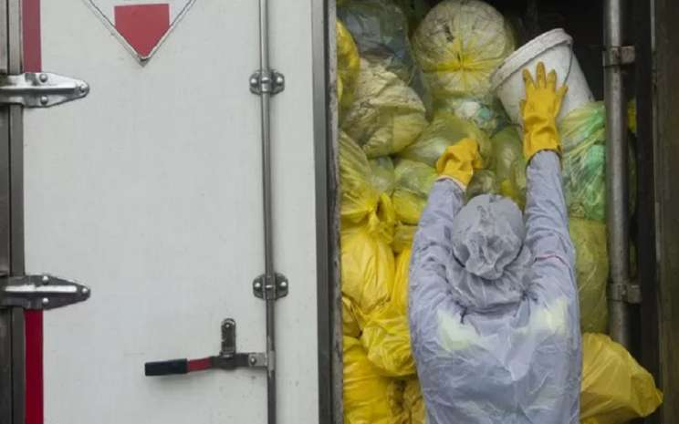 Petugas memindahkan kantong-kantong berisi masker habis pakai dari truk milik Dinas Lingkungan Hidup (DLH) DKI Jakarta ke truk milik PT Wastec Internasional di Dipo Sampah Ancol, Jakarta, Rabu (15/7/2020).  - Antara