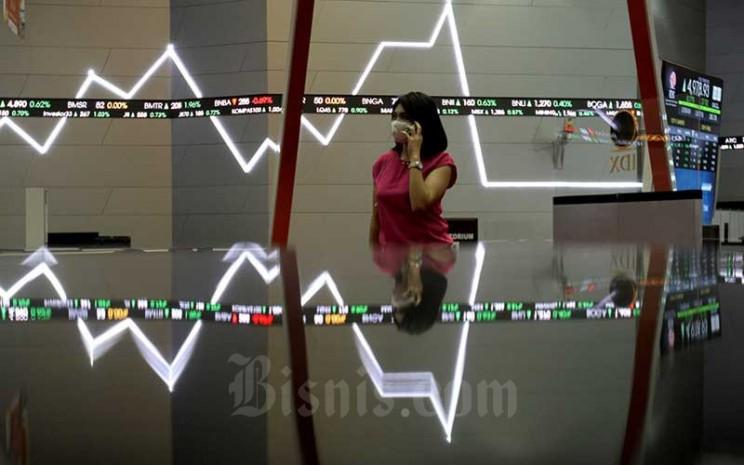 Karyawati beraktivitas di sekitar grafik pergerakan Indeks Harga Saham Gabungan (IHSG) di PT Bursa Efek Indonesia, Jakarta, Kamis (4/6/2020). Bisnis - Arief Hermawan P
