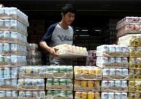 Pekerja menyusun aneka jenis minuman kaleng di salah satu grosir penjual makanan dan minuman kemasan di Pekanbaru, Riau, Senin (12/6)./Antara-Rony Muharrman