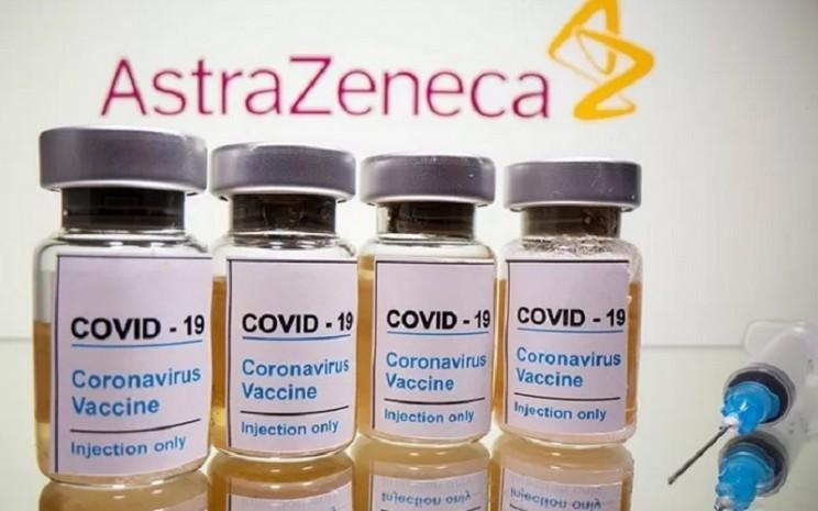 """Botol dengan stiker bertuliskan, """"Covid-19 vaksin Coronavirus Injeksi"""" dan jarum suntik medis terlihat di depan logo AstraZeneca yang ditampilkan dalam ilustrasi (31/10/2020). - Antara/Reuters"""