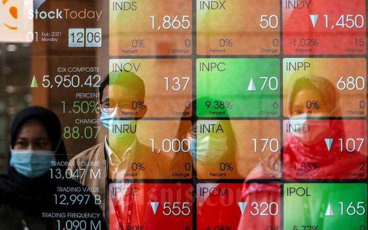 Pekerja melintasi papan elektronik yang menampilkan pergerakan Indeks Harga Saham Gabungan (IHSG) di Bursa Efek Indonesia, Jakarta, Senin (1/2/2021)./Bisnis - Eusebio Chrysnamurti