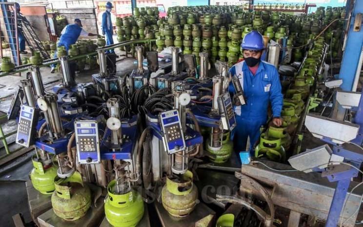 Petugas melakukan tahap pengisian LPG pada tabung gas 3kg di SPBE Srengseng, Jakarta, Senin (1/2/2021). Bisnis - Eusebio Chrysnamurti