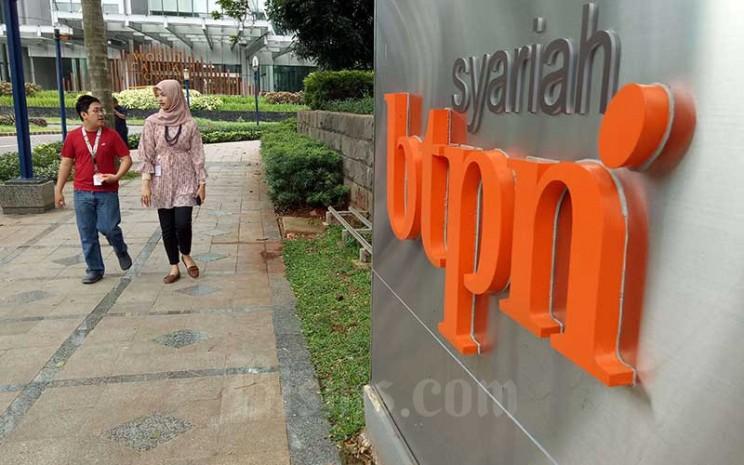 Pejalan kaki berjalan melewati logo PT Bank Tabungan Pensiunan Nasional Syariah Tbk atau BTPN Syariah di Jakarta, Senin (13/1/2020). Bisnis - Dedi Gunawan\\n