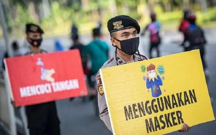 Personel gabungan TNI dan Polri membagikan masker saat kampanye Protokol Kesehatan Covid-19 di kawasan Pasar Tanah Abang, Jakarta, Minggu (31/1/2021). - Antara