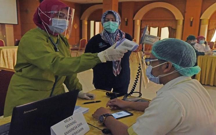 rnPetugas memeriksa kondisi fisik tenaga medis sebelum menyuntikan vaksin CoronaVac, di RS Islam Sari Asih Serang, Banten, Sabtu (16/1/2021). Menurut Kepala Dinas Kesehatan Provinsi Banten Ati Pramuji sebanyak 81 ribu tenaga medis yang melayani pasien COVID-19 di Banten akan divaksin secara bertahap hingga Februari 2021. - Antara\\r\\n
