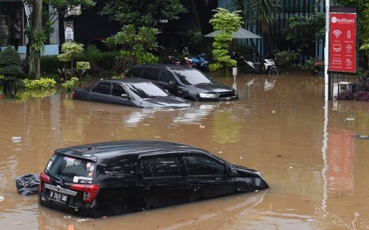 Pengendara mobil boks ekspedisi menerobos genangan air hujan di kolong Jembatan Cawang, Jakarta Timur, Jumat (19/2/2021). - Antara