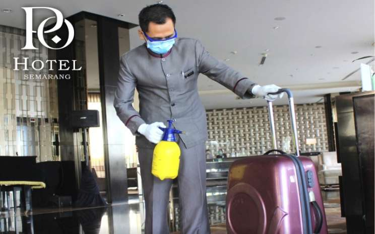Petugas concierge PO Hotel Semarang menyemprotkan disinfektan ke barang bawaan tamu sebelum mengantarnya ke kamar.