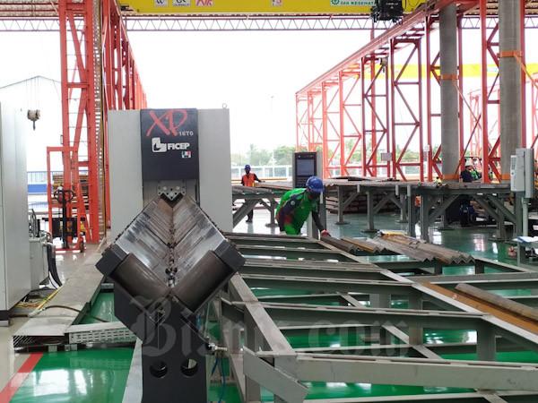 Pekerja pabrik menyusun bagian menara saluran tegangan ekstra tinggi (SUTT) yang baru saja di olah dari baja canai panas (HCR) di pabrik PT Waskita Karya Infrastruktur. Pabrik tersebut memiliki kapasitas produksi bagian menara SUTET 48.000 ton per tahun.