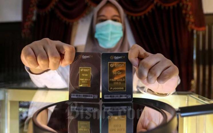 Karyawan menunjukan emas di Galeri 24 Pegadaian, Jakarta, Kamis (18/2/2021). Bisnis - Eusebio Chrysnamurti