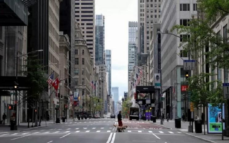 Seorang pria bersama anjing peliharaannya berjalan di kawasan toko-toko mewah yang tutup akibat merebaknya Covid-19 di Jalan 5th, Manhattan, Kota New York, New York, Amerika Serikat, Senin (11/5/2020). - Antara/Reuters\\r\\n