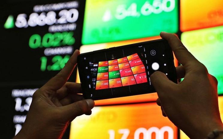 Pengunjung memotret layar monitor perdagangan Indeks Saham Gabungan (IHSG) di Bursa Efek Indonesia, Jakarta, Senin (17/2/2020). Bisnis - Eusebio Chrysnamurti