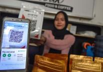 Seorang warga menggunakan pembayaran nontunai Quick Response Indonesia Standard (QRIS) saat membeli kopi di warung kopi Jalik Rumbuk di Mataram, NTB, Selasa (12/1/2021)./ANTARA FOTO-Ahmad Subaidi