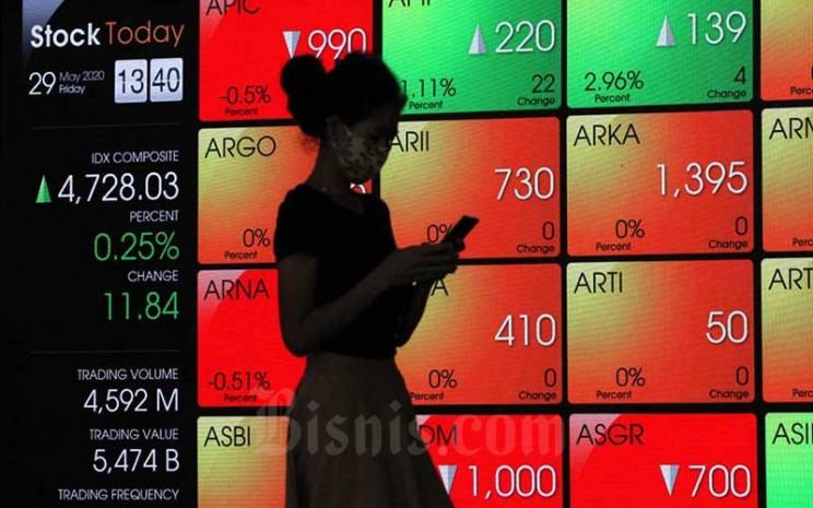 Pengunjung berjalan di dekat papan elektronik yang menampilkan perdagangan harga saham di Jakarta, Jumat (29/5/2020). Bisnis - Dedi Gunawan
