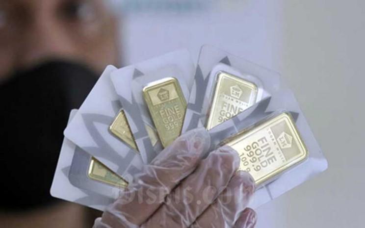 Karyawan menunjukan emas logam mulia di Butik Antam, Jakarta, Kamis (14/1/2021). Bisnis - Himawan L Nugraha