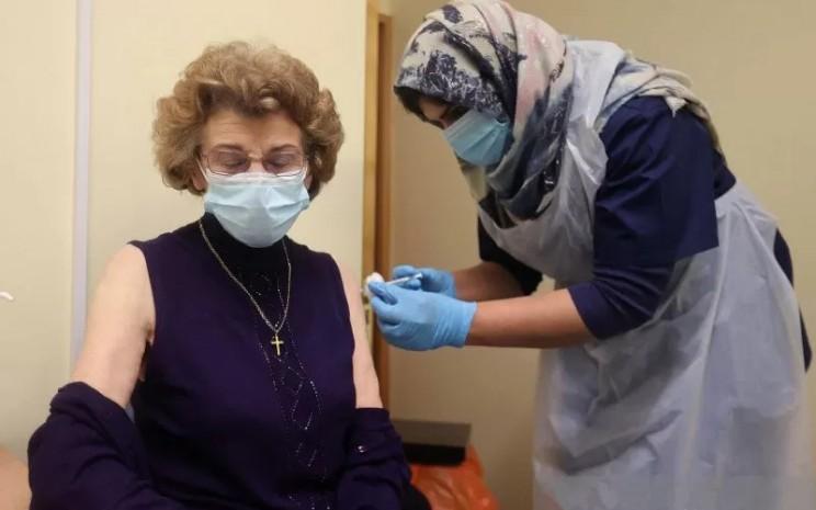 Seorang pasien menerima suntikan pertama dari dua suntikan vaksin Covid-19 buatan Pfizer/BioNTech di ruang operasi di Wolverhampton, Inggris, Senin (14/12/2020).  - REUTERS/Antara