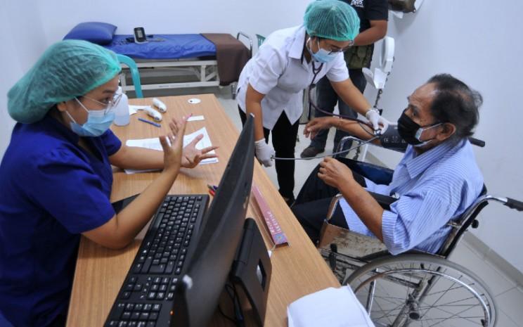 Petugas melakukan pemeriksaan awal kepada warga lanjut usia (lansia) yang akan menjalani vaksinasi Covid-19 di Rumah Sakit Bali Mandara, Denpasar Bali, Rabu (24/2/2021). - Antara