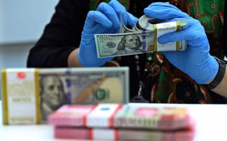 Karyawan menunjukan Rupiah dan Dolar AS di Jakarta, Rabu (27/1/2021). Nilai tukar rupiah di pasar spot ditutup menguat 15 poin atau 0,11 persen menjadi Rp14.050 per dolar AS. Bisnis - Eusebio Chrysnamurti